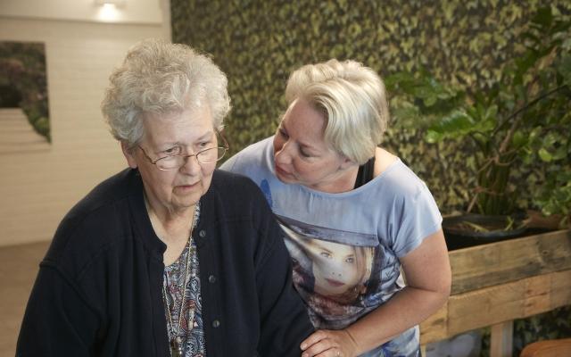 Verzorgende Jacqueline Buijs schenkt aandacht aan bewoonster Kloek